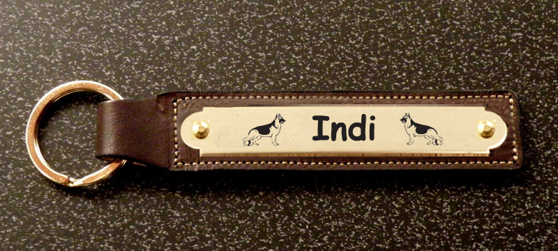Custom engraved brass herding dog design nameplate on a leather key fob.