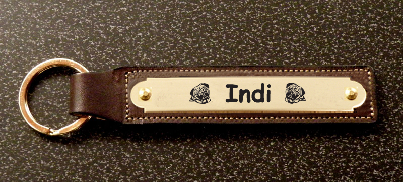 Custom engraved brass toy dog design nameplate on a leather key fob.